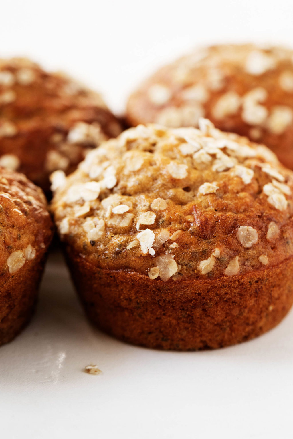 A zoomed in, close up of vegan banana oat chia muffins, freshly sprinkled with rolled oats.