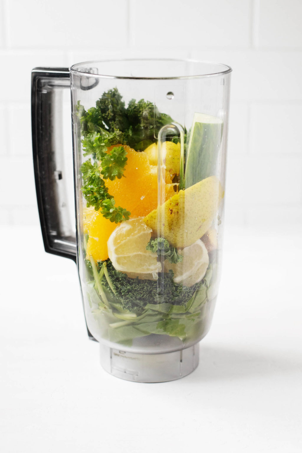 A clear blender is filled with healthful, plant-based ingredients.