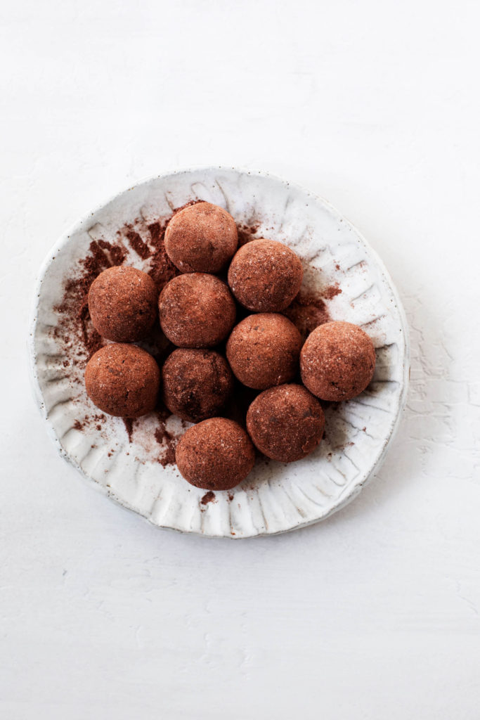 A plate of raw vegan brownie bites, rolled in cacao powder to resemble truffles.