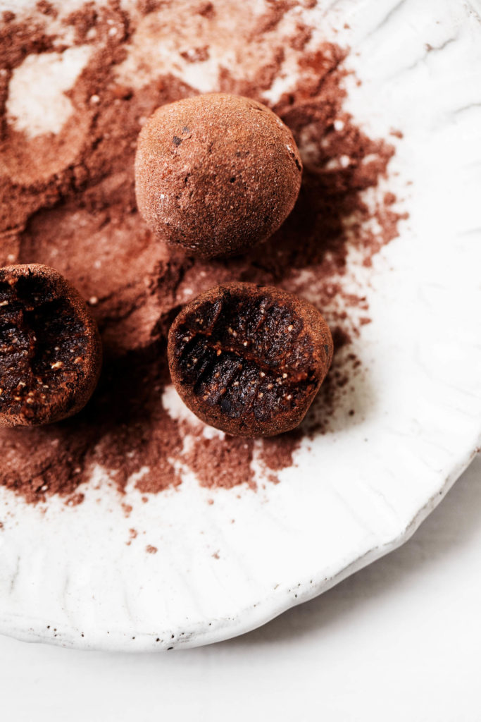 Sweet, luscious raw vegan brownie bites, freshly dusted in cacao powder and served on a plate.