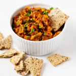 A white ramekin has been filled with a lentil sweet potato salad and is accompanied by crackers.