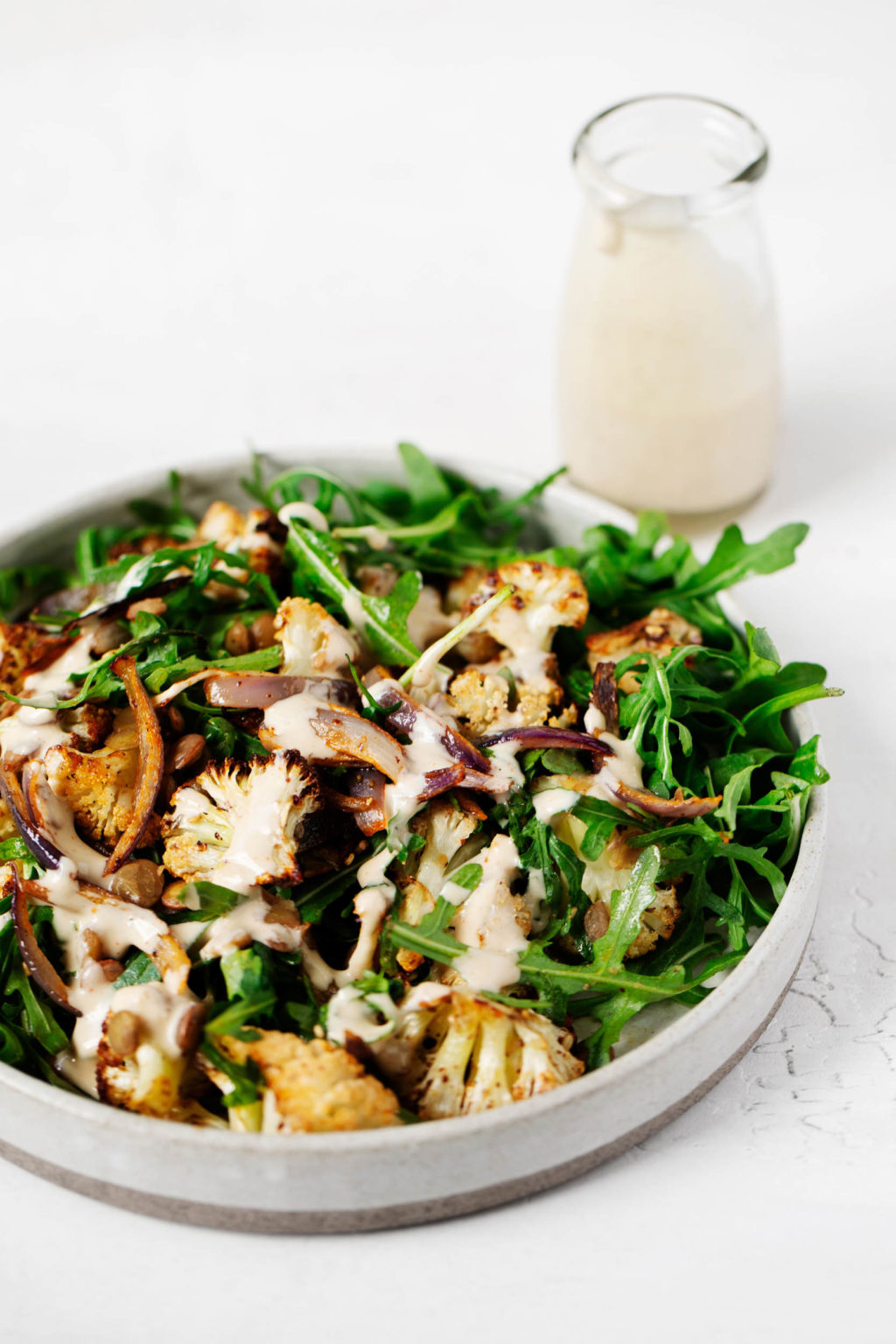 A za'atar roasted cauliflower and green salad has been plated against a white surface. Extra tahini dressing is in a glass container in the background.