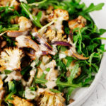 A white plate has been covered with a vibrant salad of za'atar roasted cauliflower, red onion, lentils and greens.