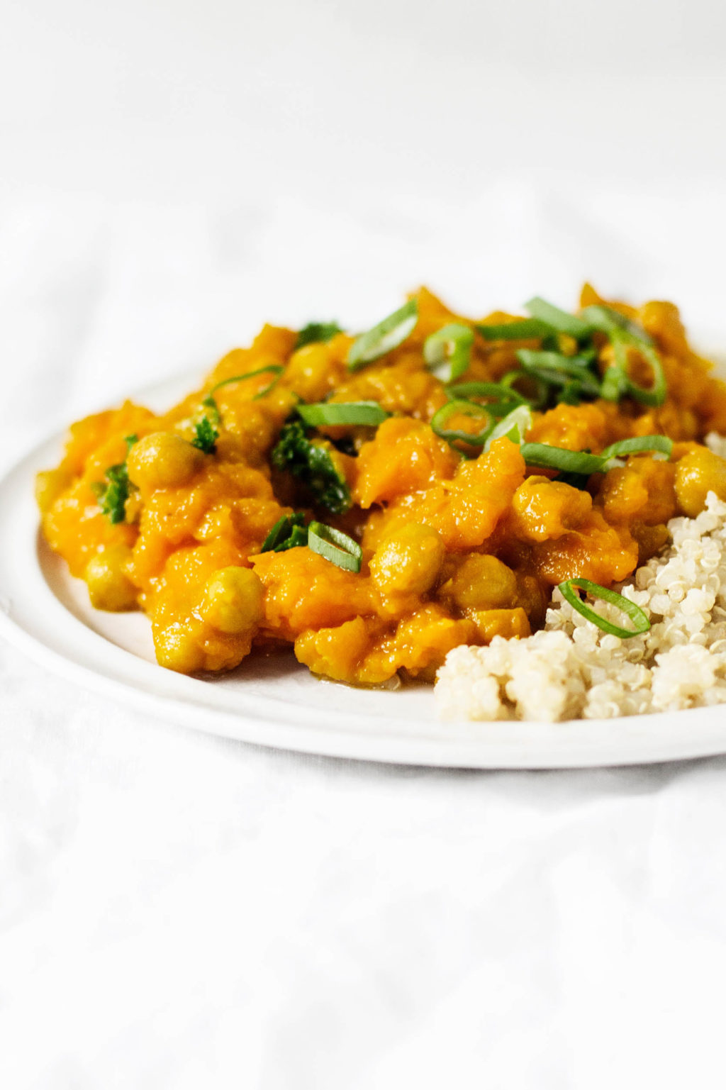 Curried butternut squash, golden raisins, and chickpeas make for a hearty and delicious winter meal. They're served with chopped green onions and cooked quinoa.