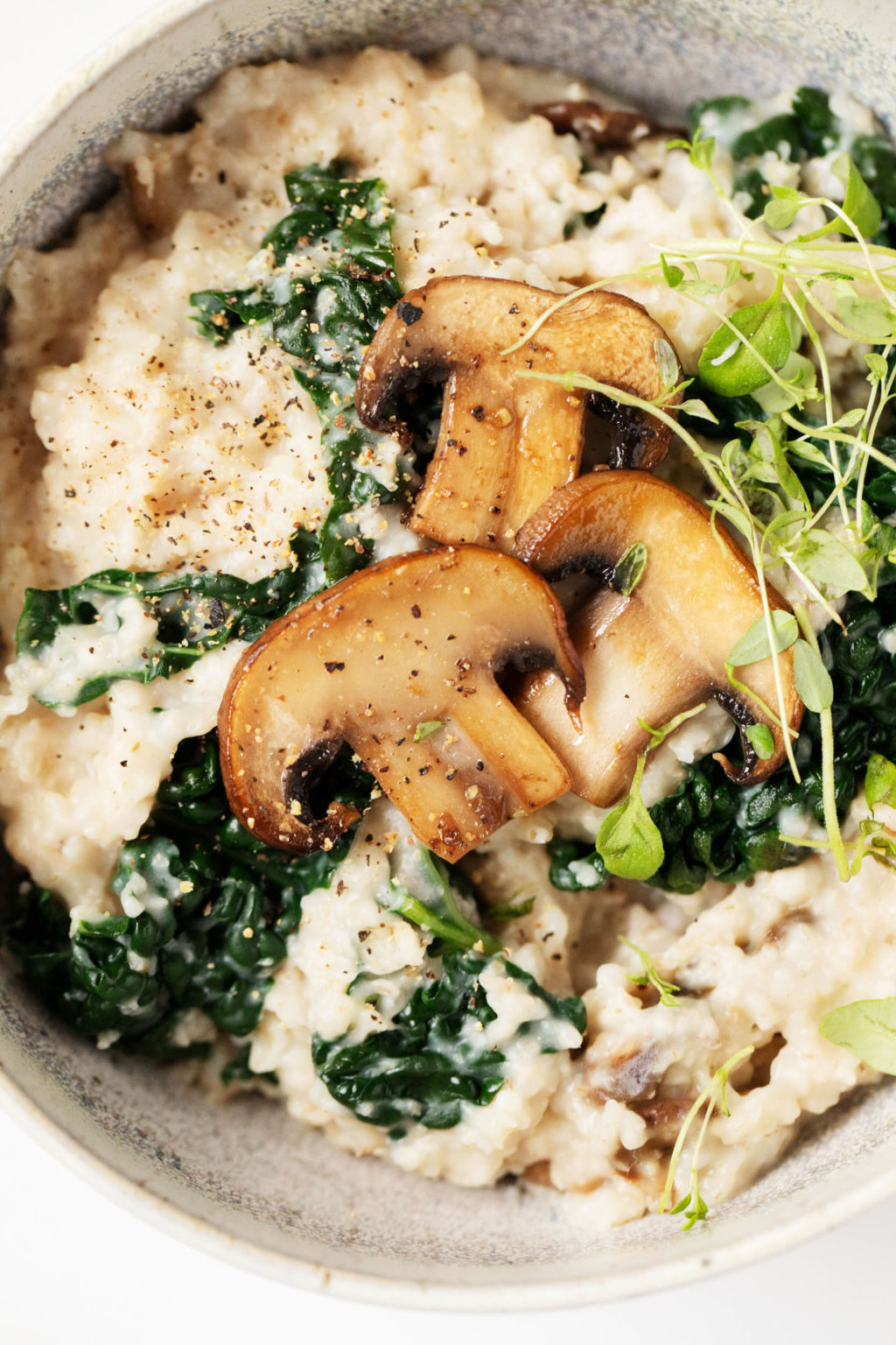 A close up photograph of a savory, whole grain breakfast with mushrooms and greens.