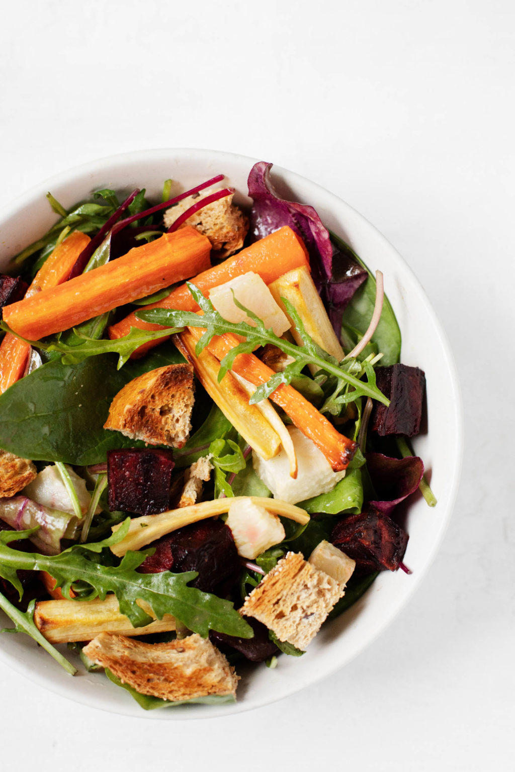 A round bowl containing the colorful ingredients of a wintertime salad, including greens, carrots, parsnips, and beets.