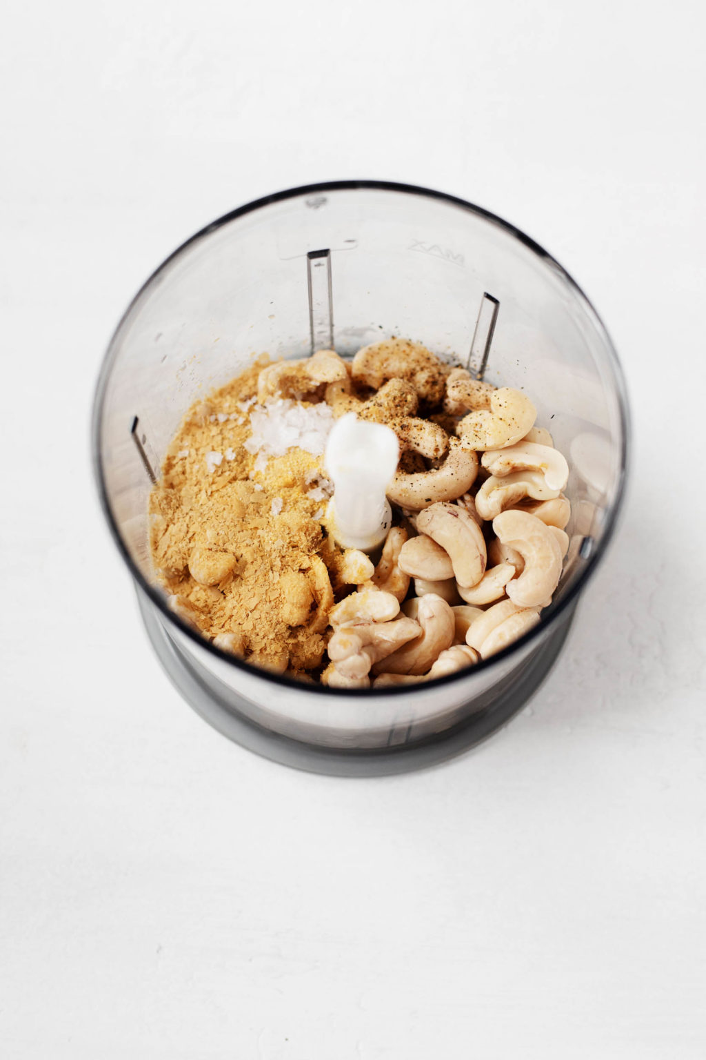A food processor is full of raw cashews, nutritional yeast, and salt, ready for blending.