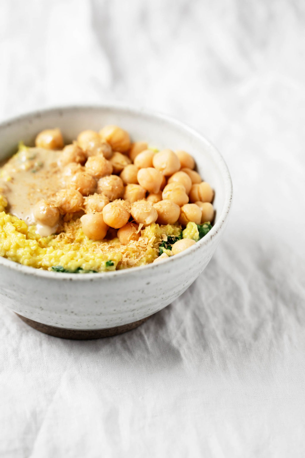 An angled shot of a bowl of savory oatmeal, which has been topped with tahini and chickpeas.