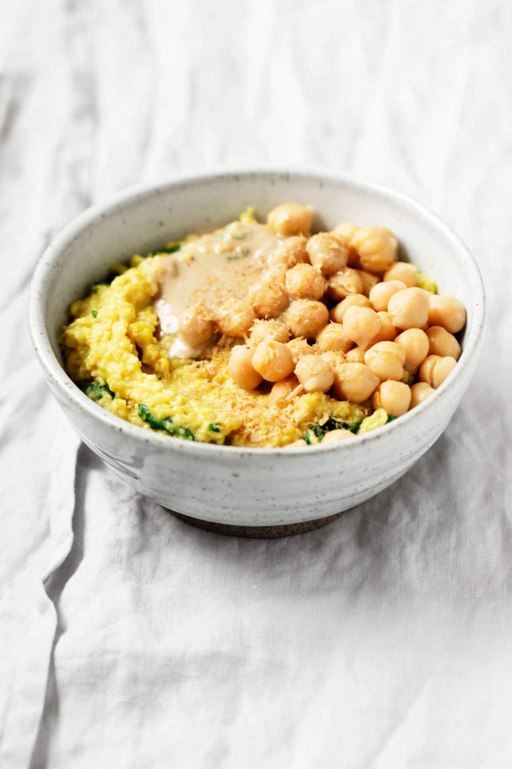 A gray and white ceramic bowl holds a dish of savory oatmeal made with chickpeas and spinach. It has been topped with a spoonful of tahini.