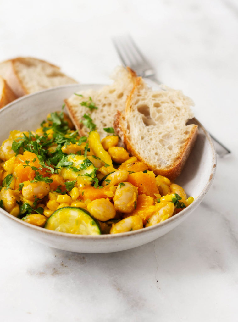 A bowl of golden succotash with butternut squash and lima beans. Served with slices of toast.