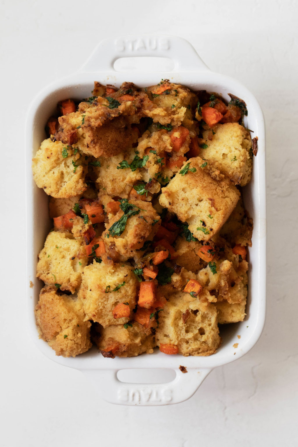 A small baking dish, filled with cornbread and vegetables.