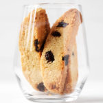 A clear glass holds several vegan cranberry almond biscotti.