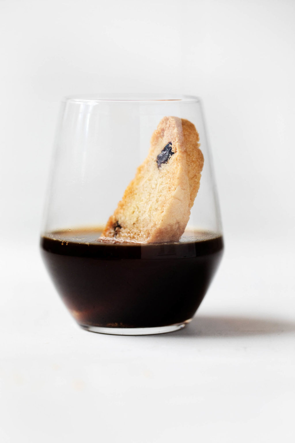 A clear glass of black coffee, with a piece of biscotti dunked inside.