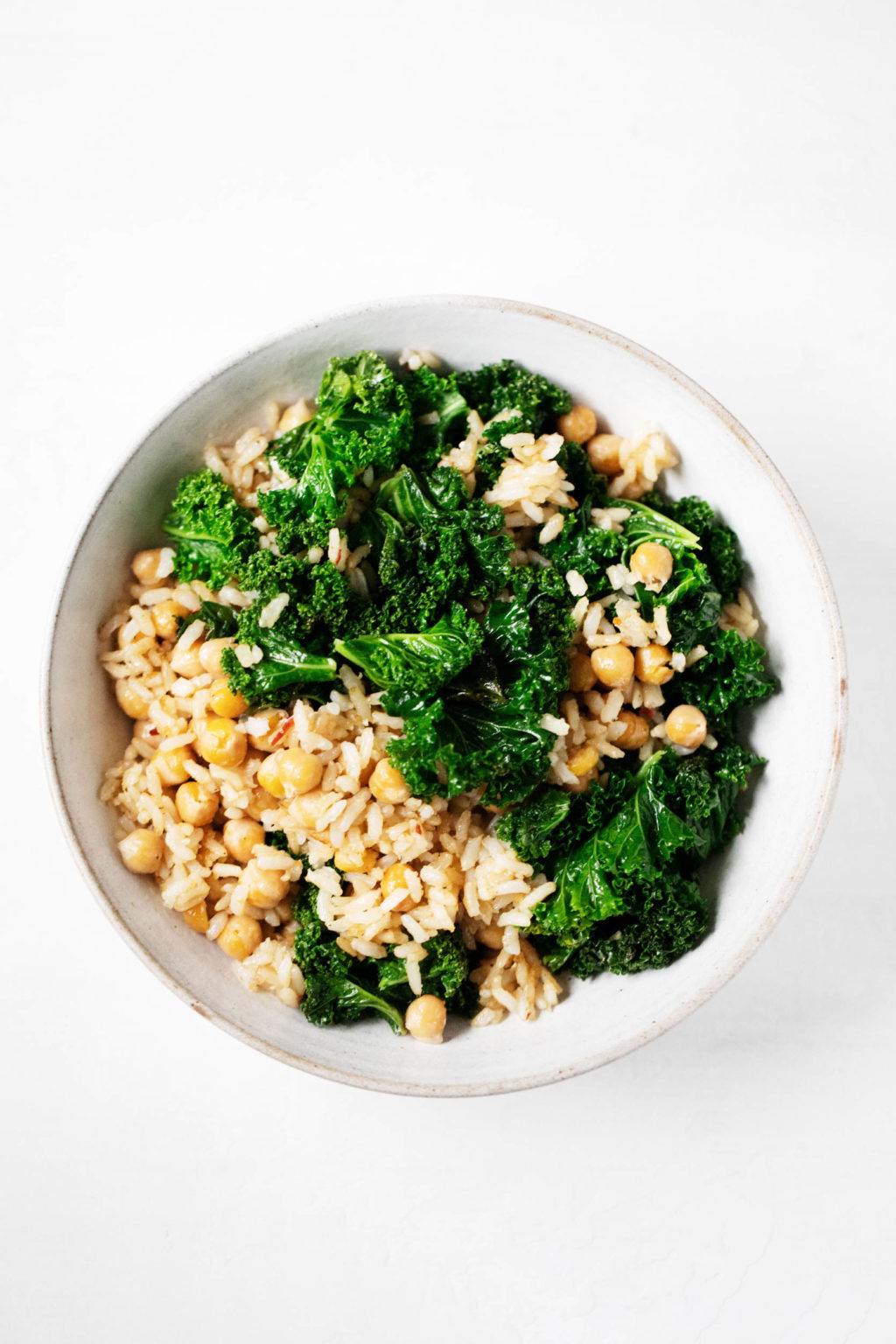 An overhead photograph of a bowl containing brown rice, greens, and chickpeas.