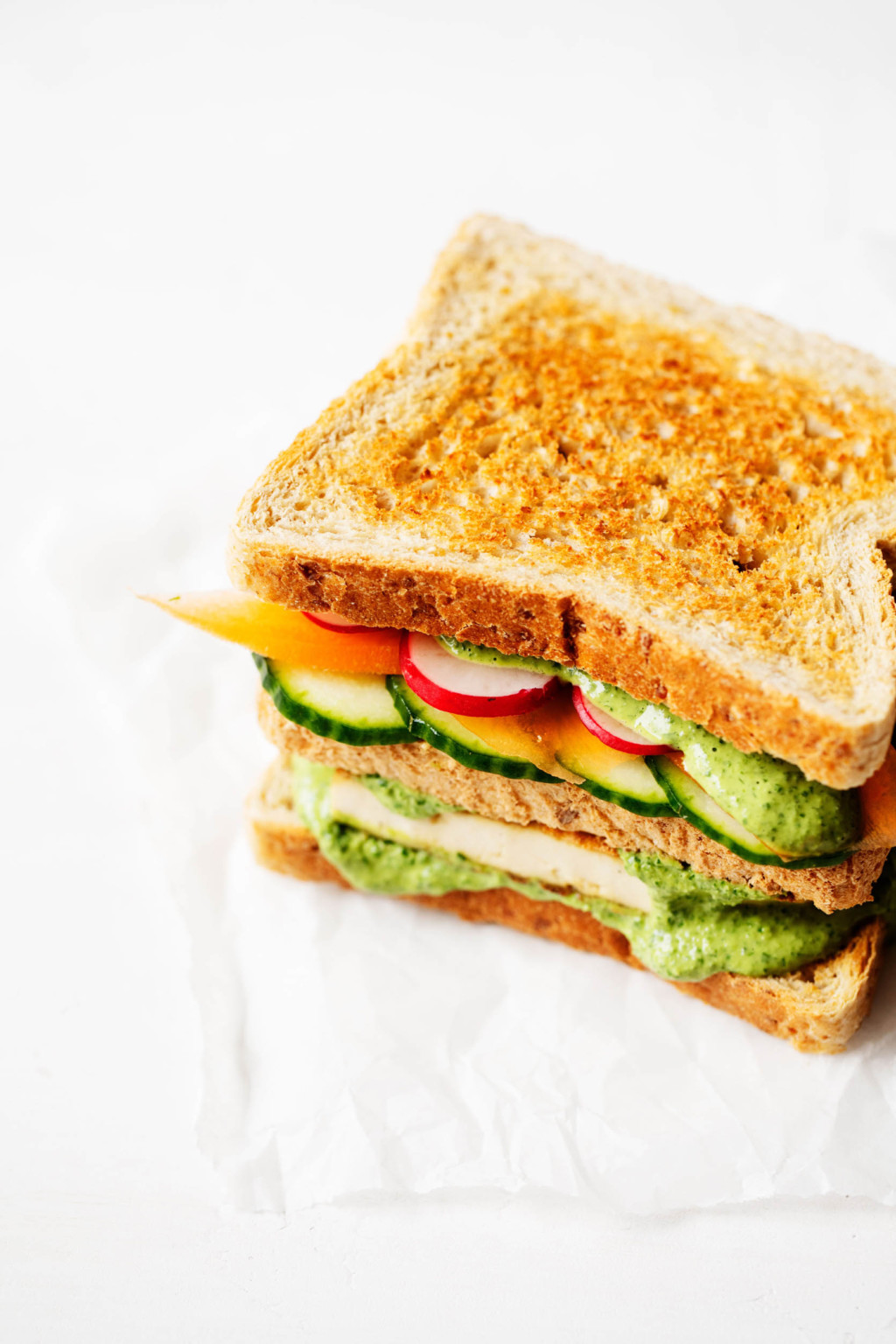 A three layered, plant based sandwich with vegetables and tofu is placed on a small piece of parchment.