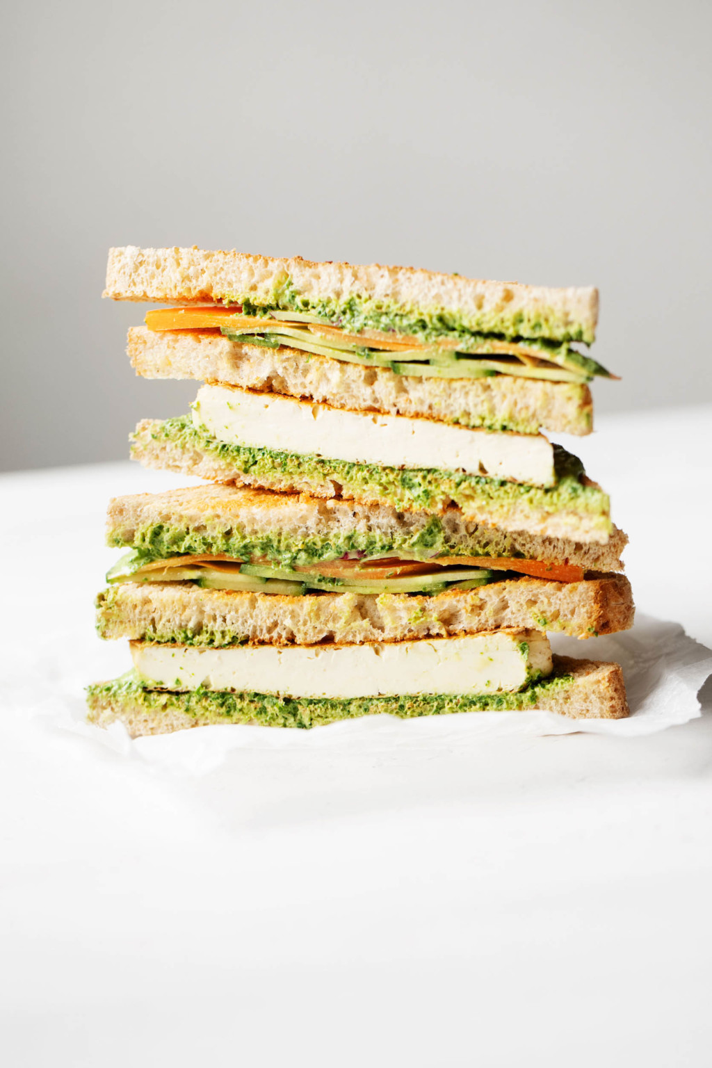 A vegan club sandwich has been sliced in half and stacked. It's filled with grilled tofu and a green sauce.