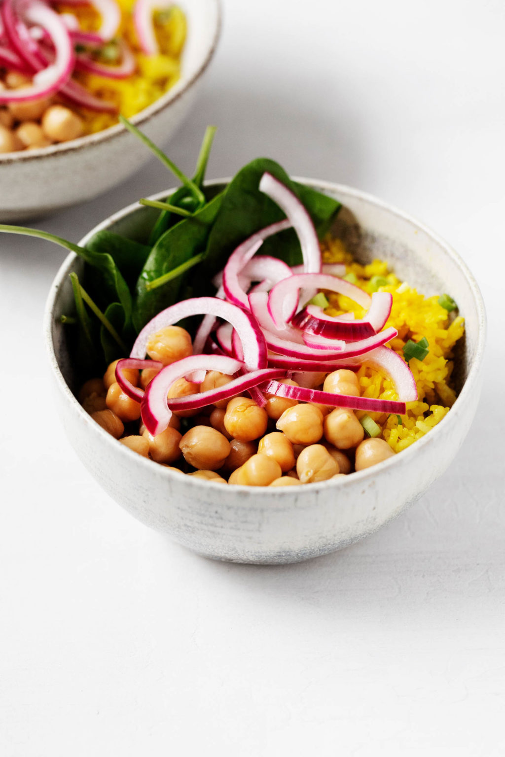 An angled photograph of two turmeric rice bowls, garnished with pink pickled onions.