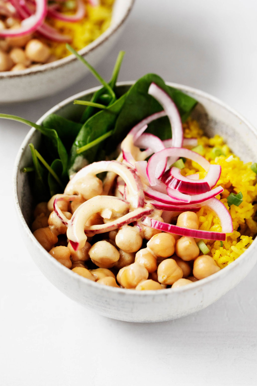 A zoomed in image of a white bowl that has been piled with spinach, onions, chickpeas, and yellow turmeric-spiced rice.