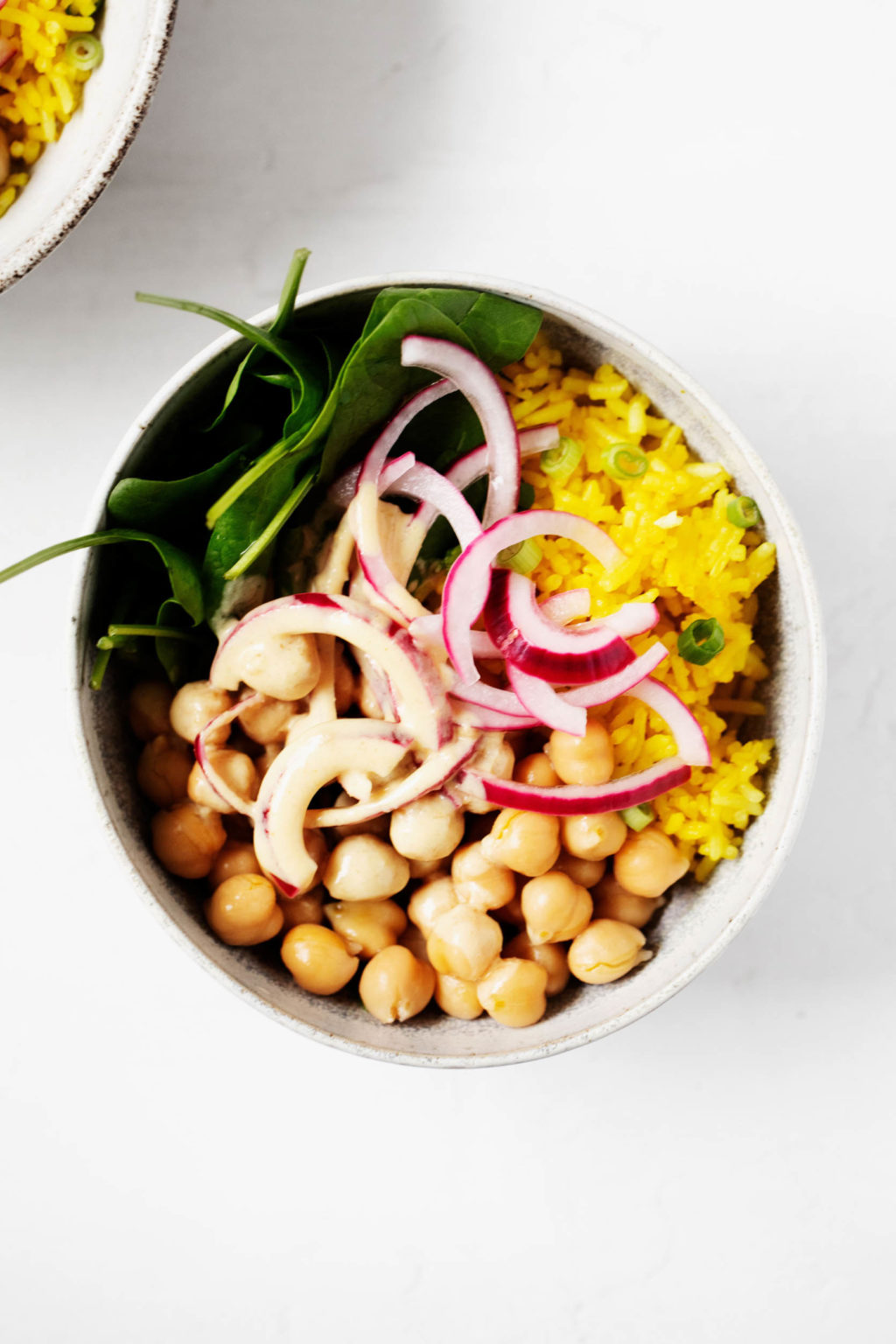 Turmeric rice bowls have been created with chickpeas, turmeric spiced rice, pickled onions, and greens. They're served in two white bowls.