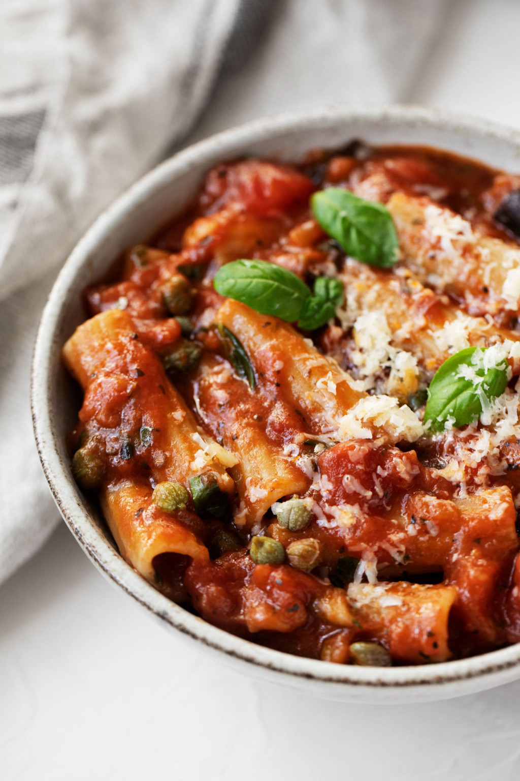 A angled photograph of a tomato and eggplant based pasta dish, which has been prepared with rigatoni and topped with small basil leaves.