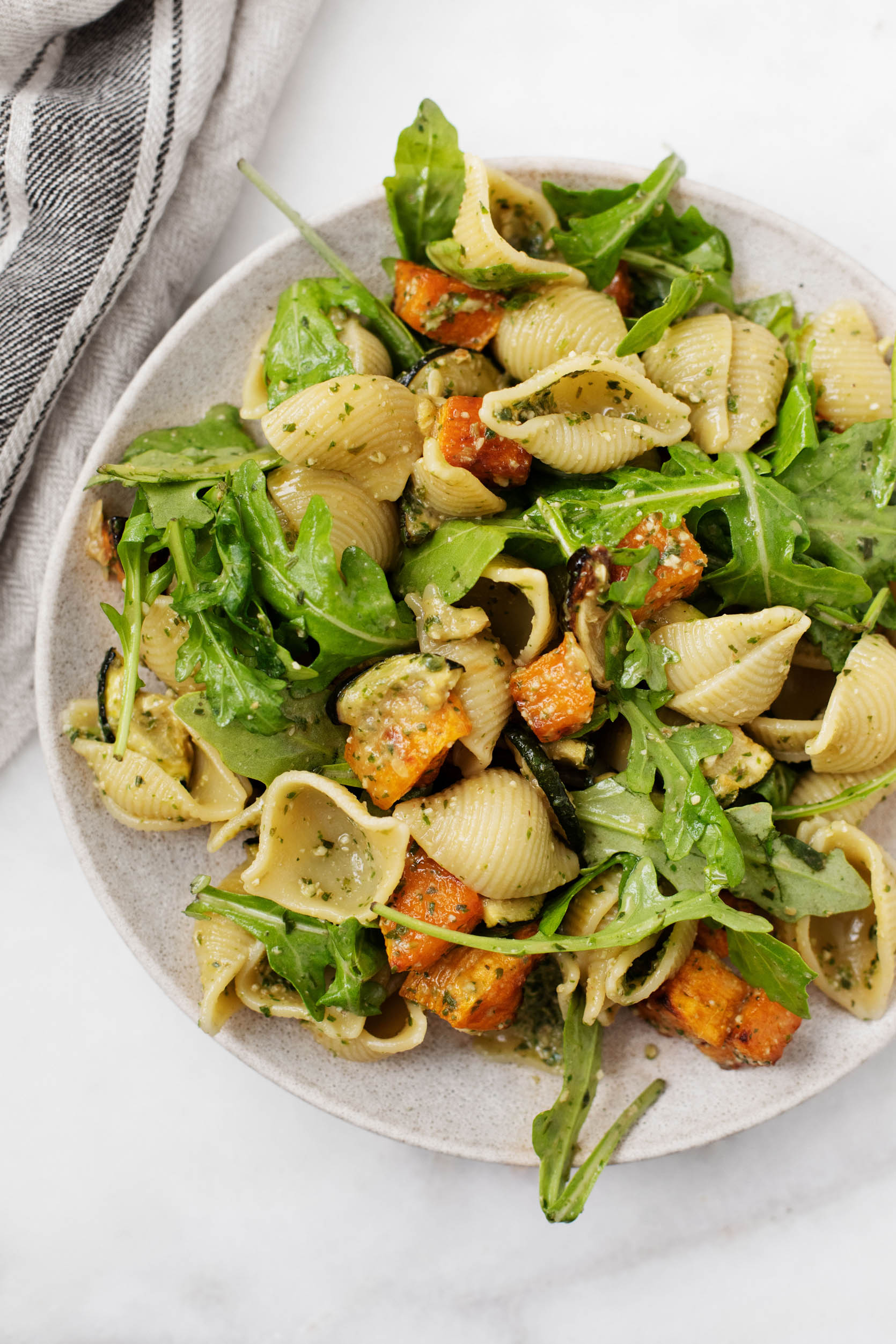 Pasta shells are dressed with freshly made pesto and tossed together with arugula, roasted butternut squash, and zucchini. They rest on a serving plate with a cloth napkin nearby.
