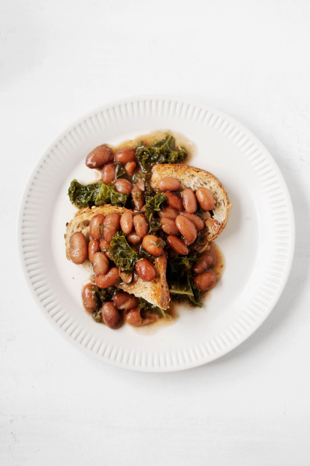 A white, fluted plate holds two slices of toast, cooked leafy greens, and a plant-based protein.