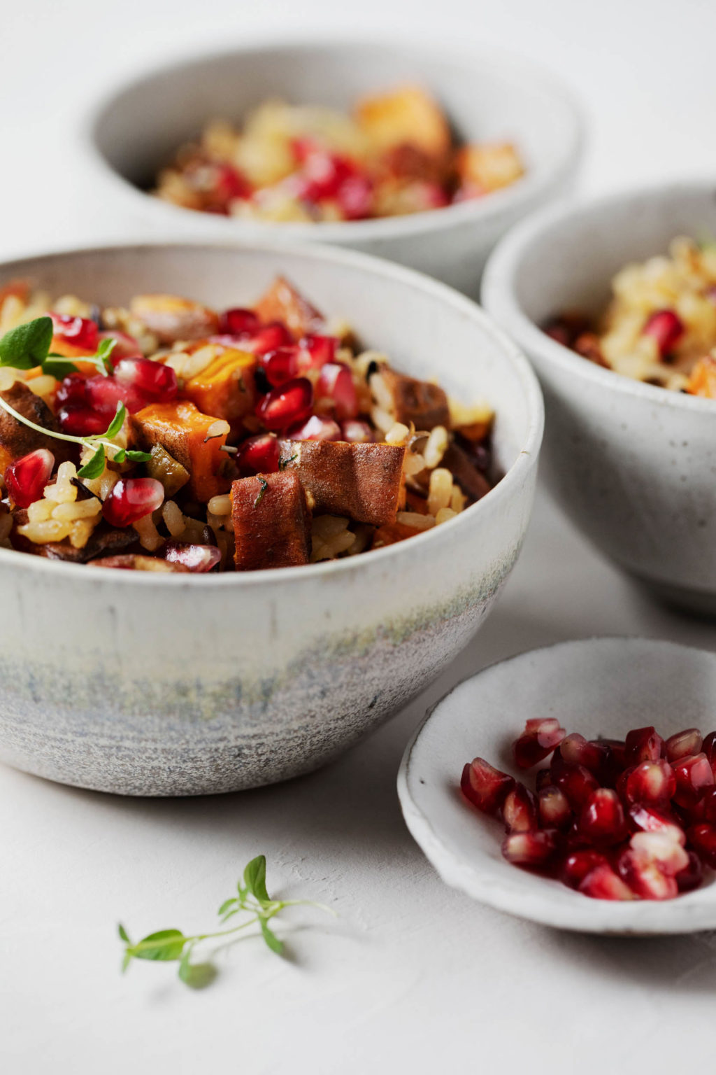 Several bowls contain the ingredients for a vegan rice and sweet potato holiday side dish.