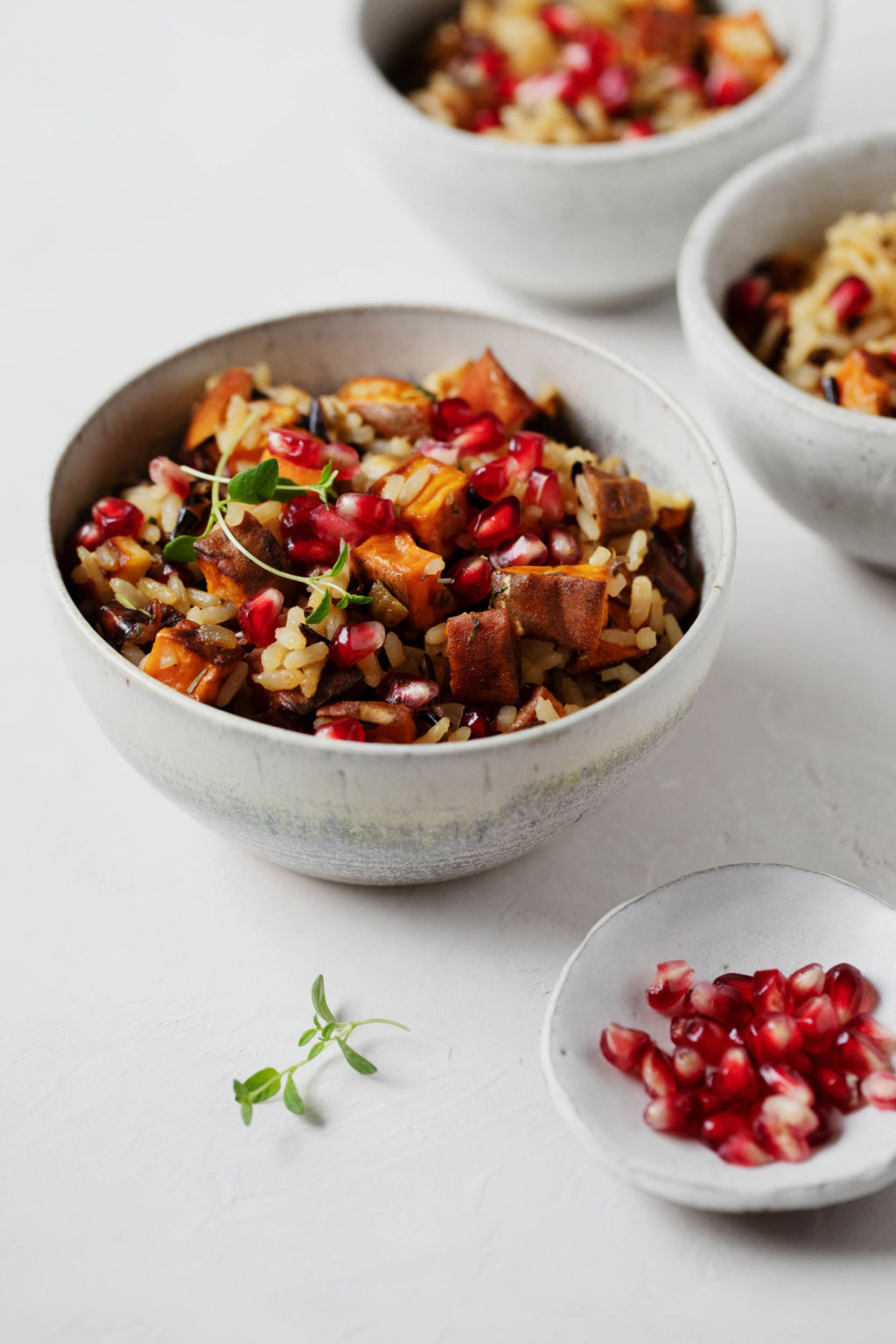 A few bowls of a vegan holiday side dish, with a small pinch bowl of pomegranate arils and fresh herbs nearby.