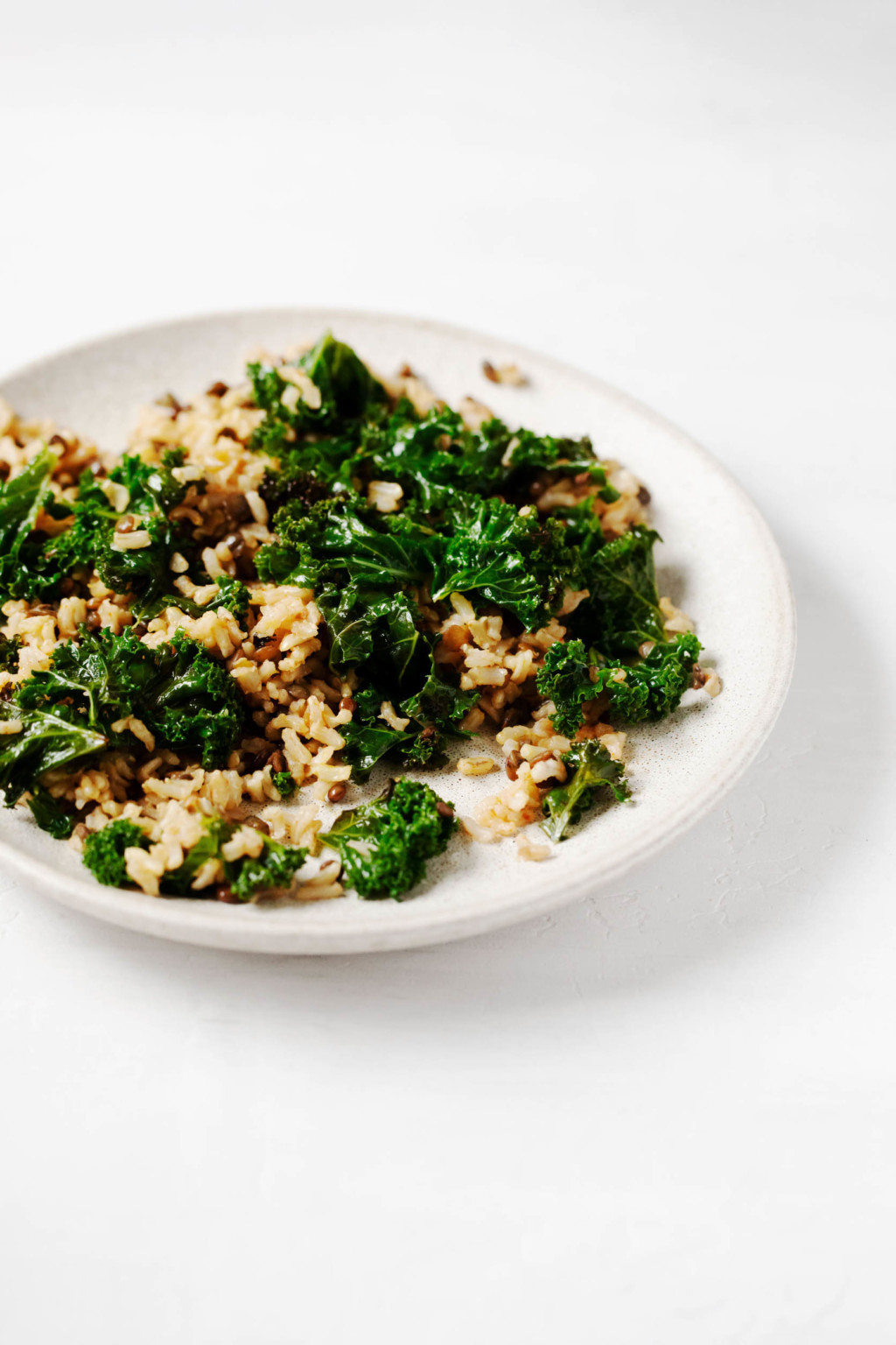 A small serving plate is covered with greens, whole grains, and legumes.