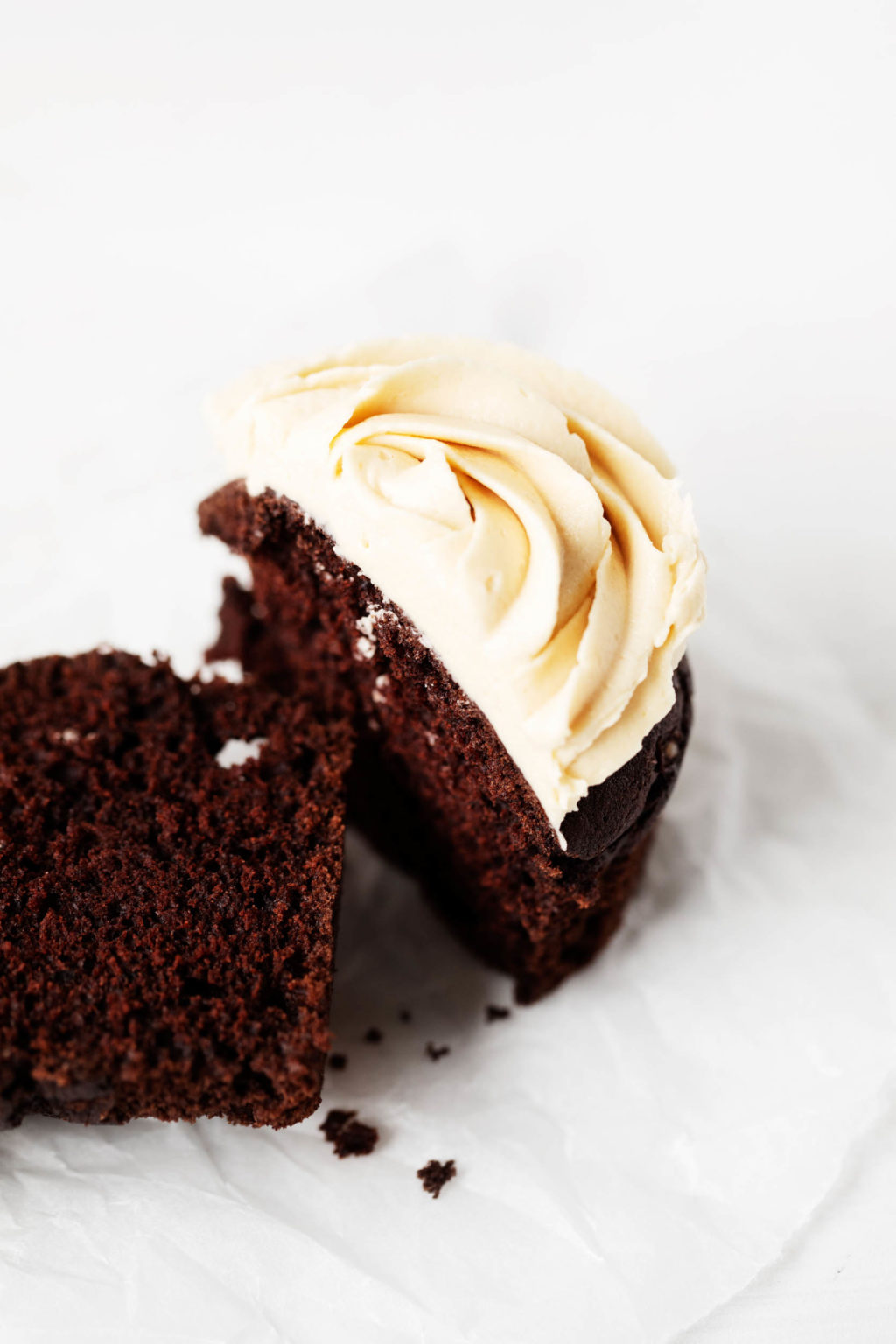 A chocolate peanut butter cupcake has been sliced neatly in half. It's resting on a small dessert plate.