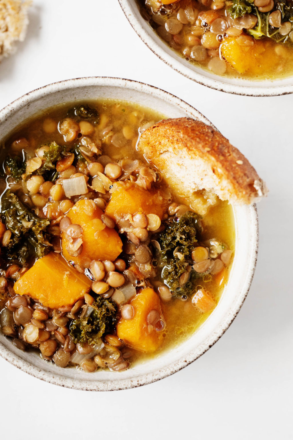 A close up photograph of a hearty vegan legume and vegetable stew, with bread poking out of the round serving bowl.