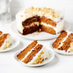 A vegan layered carrot cake is resting on a round platter. It has been sliced into three slices, which are each resting on small dessert plates against a white surface.