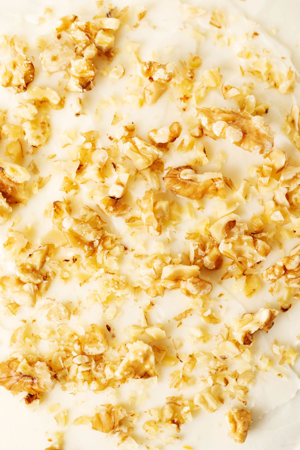 The top of a frosted cake, which has been garnished with walnuts.