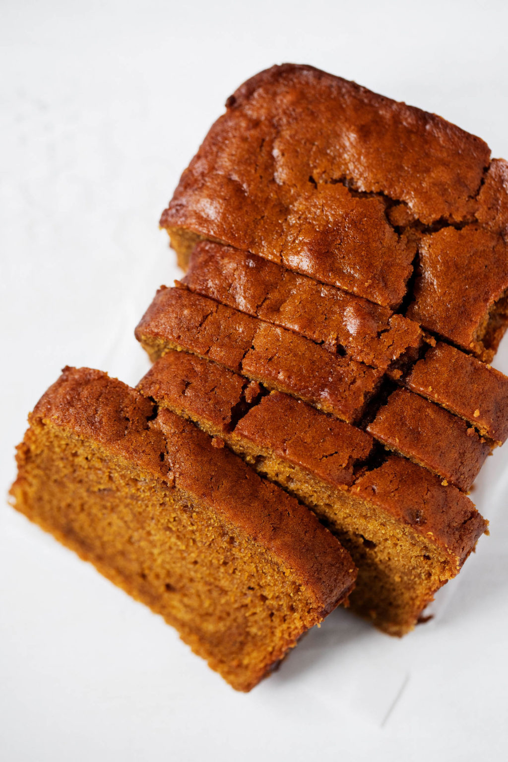 A loaf of classic vegan pumpkin bread, partially sliced and golden brown on top.