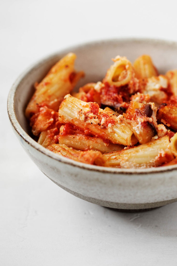 Close up of vegan baked rigatoni, with cashew tofu ricotta and juicy tomatoes.