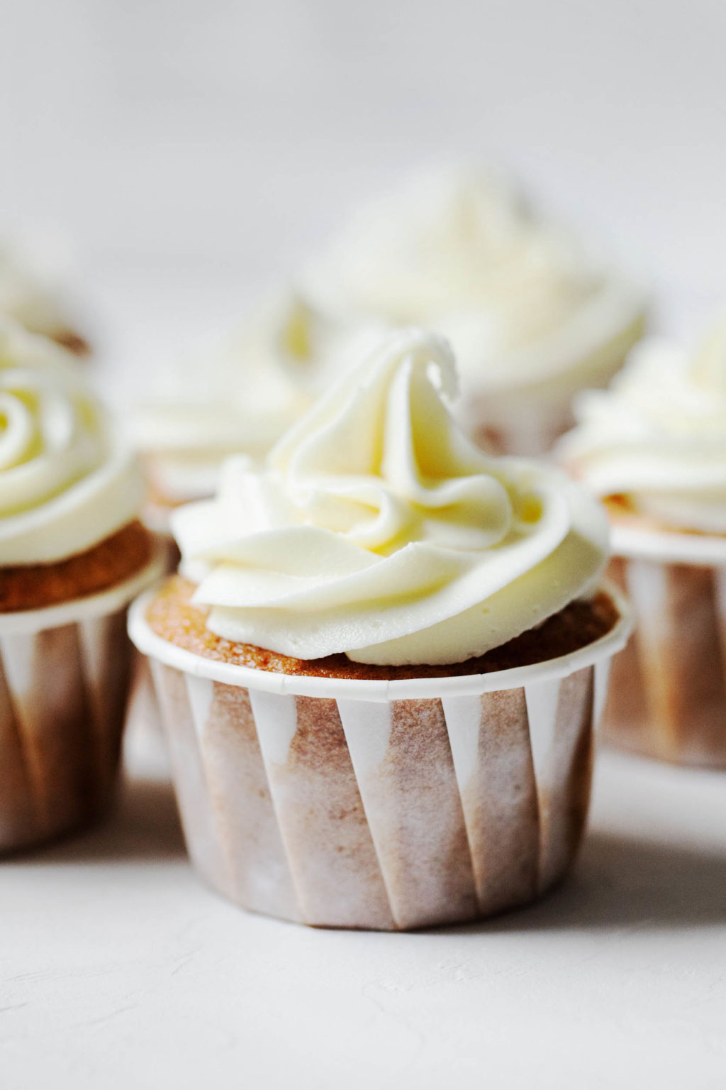 An angled photograph of vegan apple cider cupcakes, each with swirls of vegan cream cheese frosting.