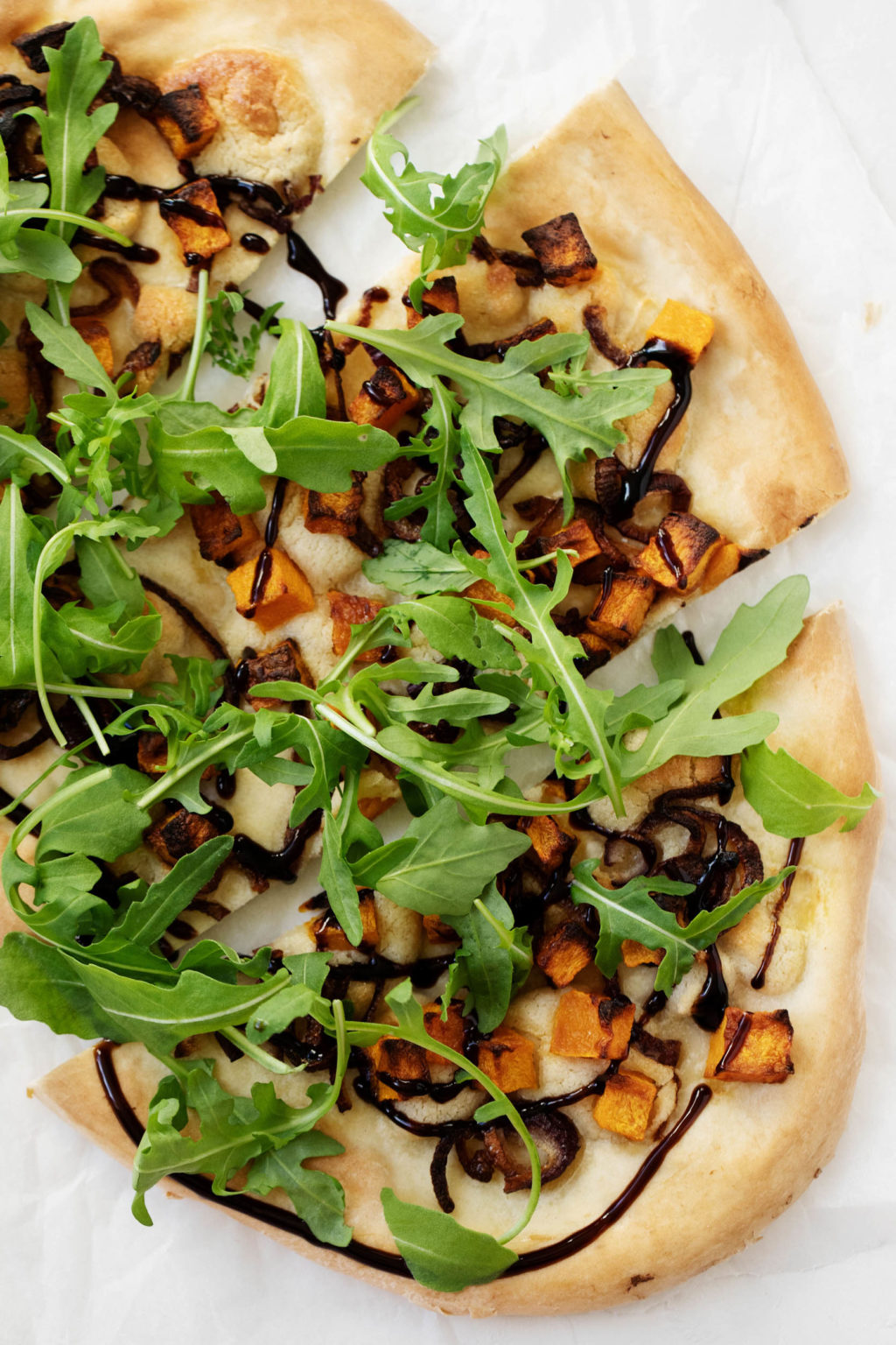 A vibrant and colorful vegan pizza for fall, topped with roasted cubes of butternuts squash, red onion, arugula, and a drizzle of balsamic glaze.