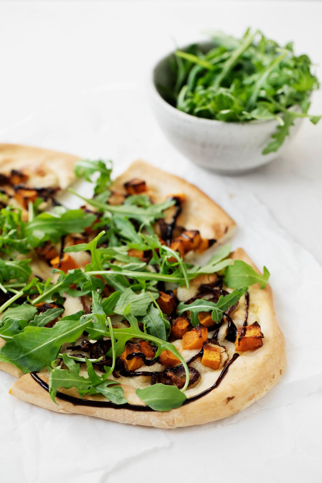 A vegan pizza with roasted butternut squash, red onions, and cashew cheese, topped with bright green arugula and drizzled with balsamic vinegar.
