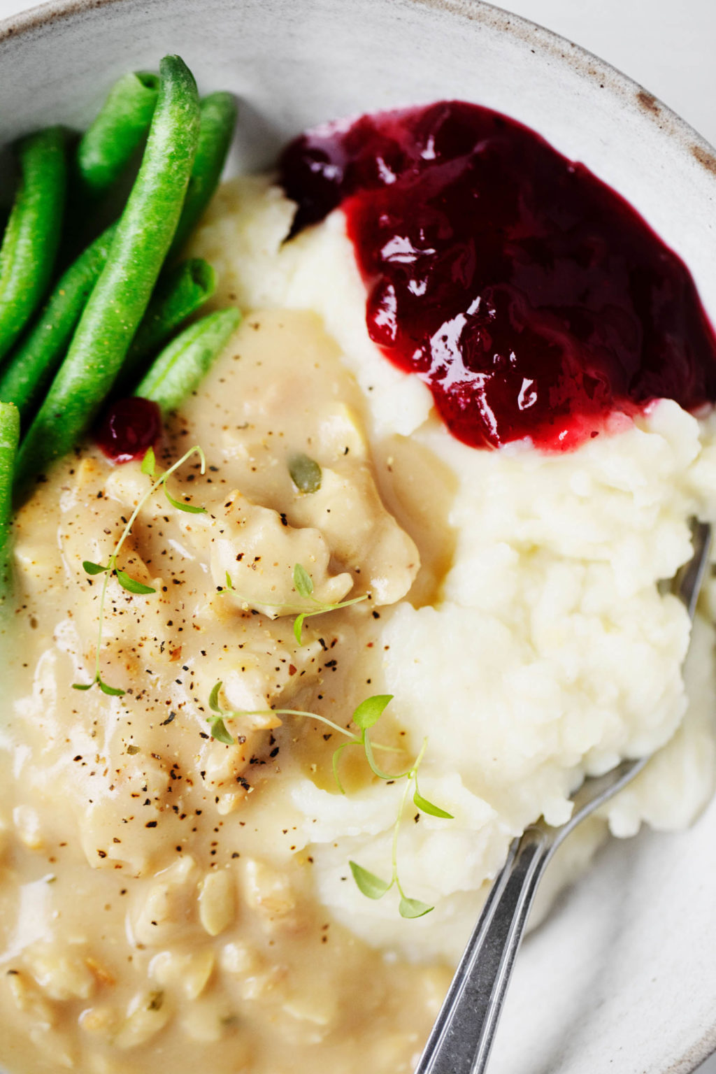 A cozy, hearty serving of traditional Thanksgiving ingredients, garnished with fresh thyme.