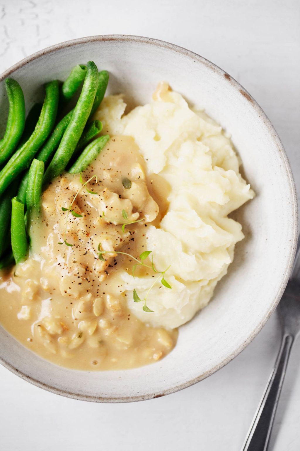 A close up of vegan mashed potatoes, topped with festive tempeh and gravy and a side of green beans.