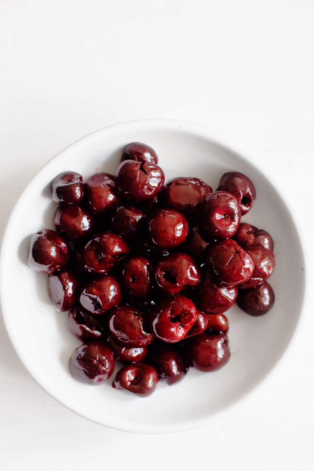 A bowl of plump and shiny dark, sweet cherries.
