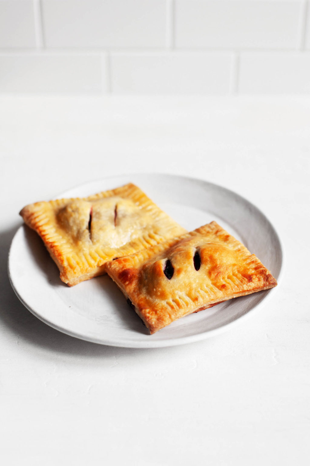 Two rectangular, vegan cherry hand pies with crispy golden pastry sit next to each other on a dessert serving plate.