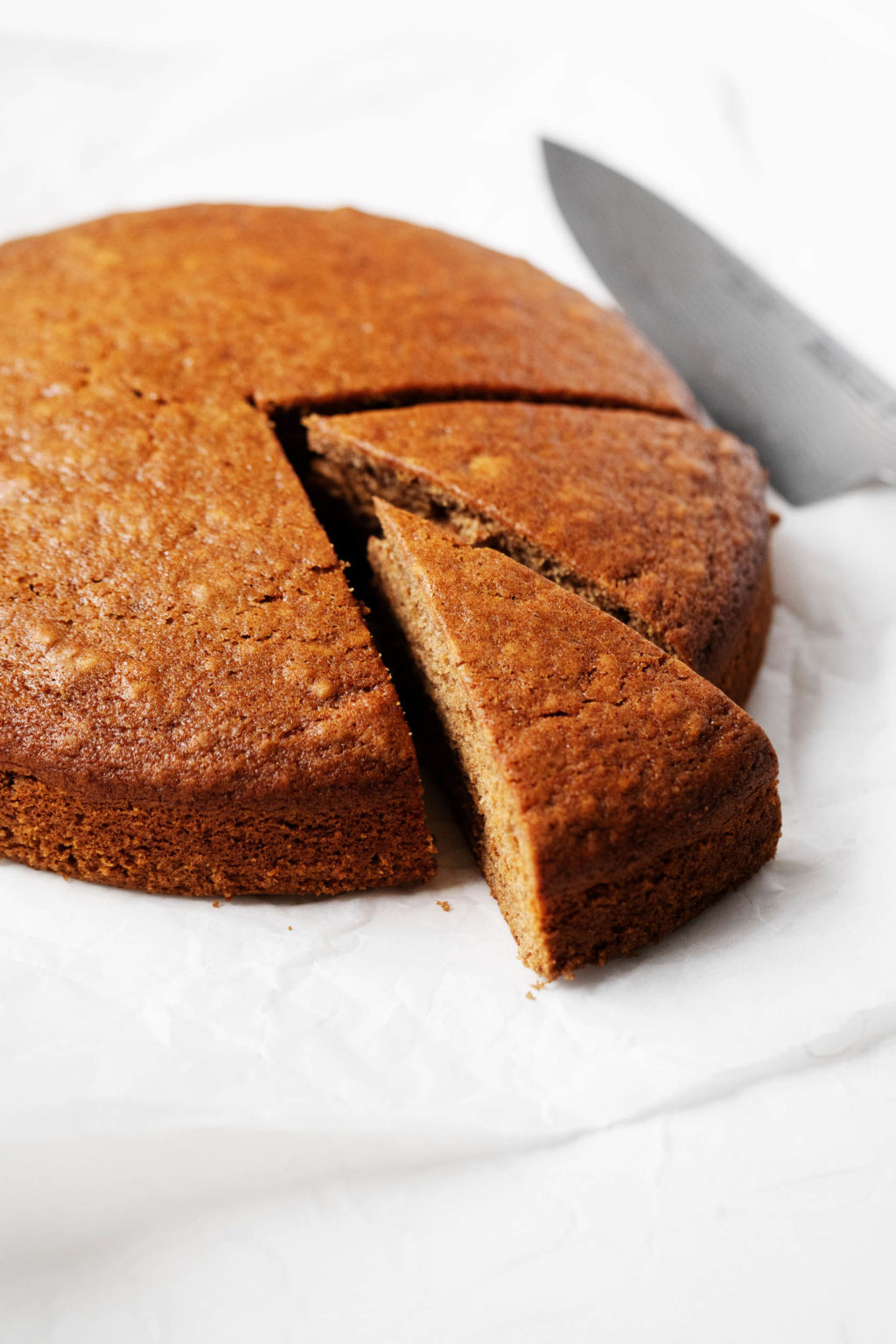 A round, golden brown gingerbread cake is being cut into slices.
