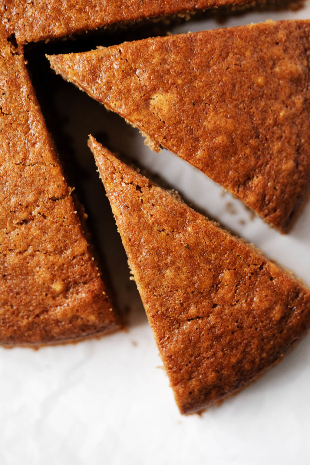 A zoomed in image of round gingerbread cake, which has just had a perfect slice cut out of it.