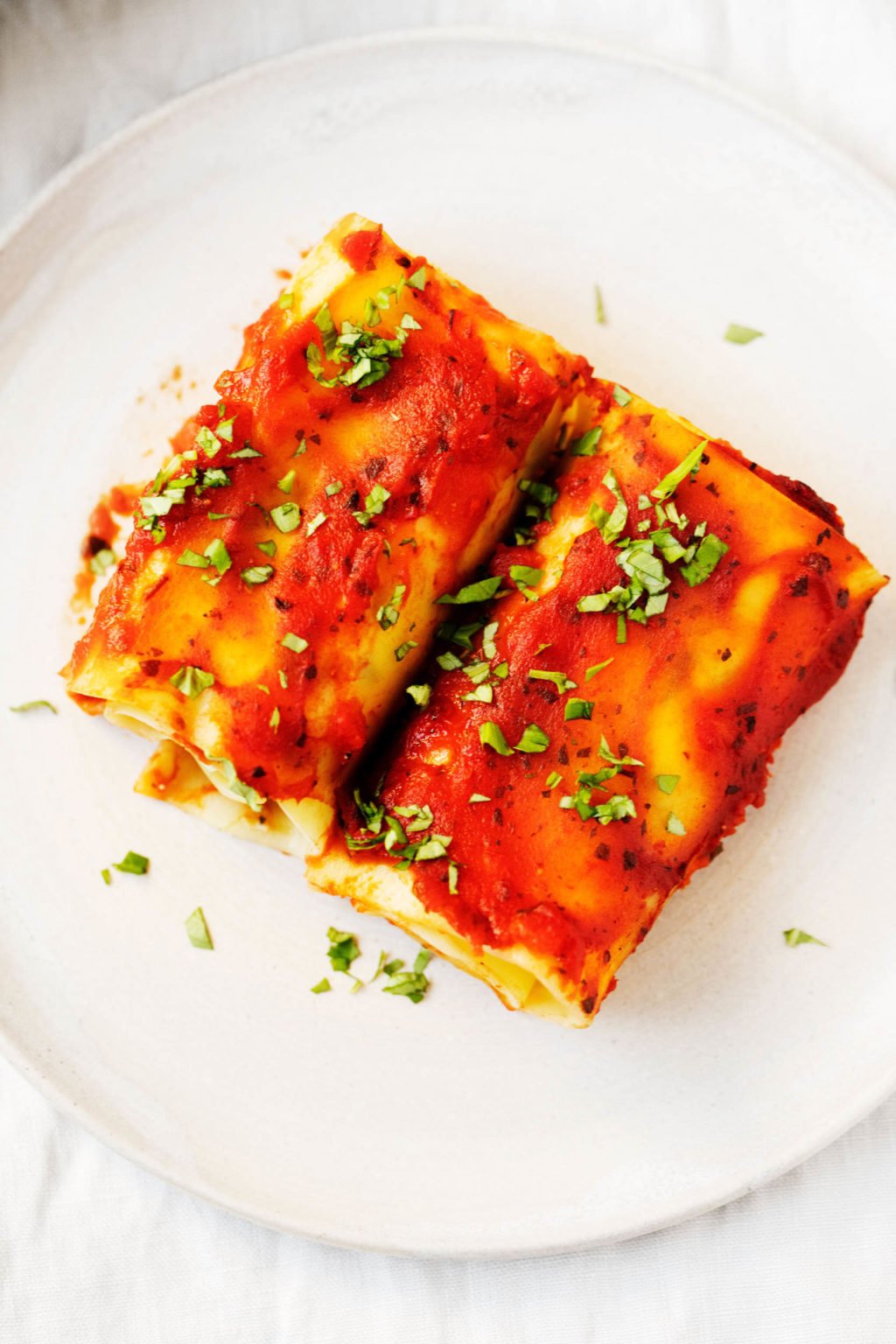 An overhead photo of two vegan lasagna rolls, sprinkled with fresh herbs.