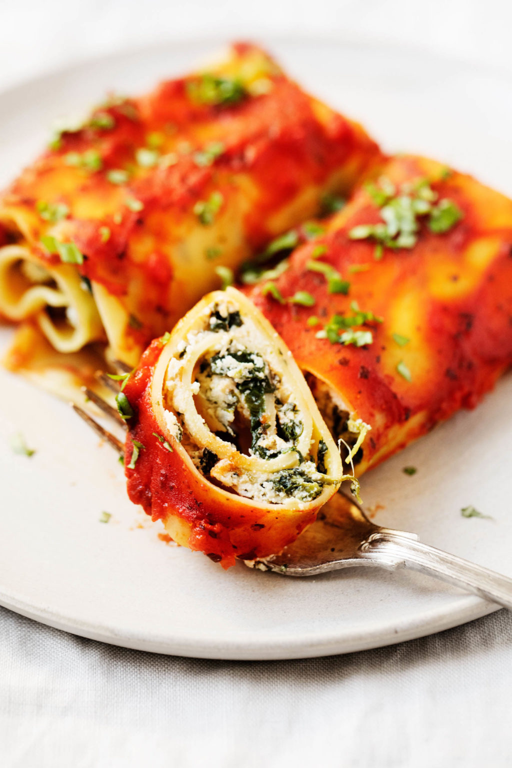 Two plant-based lasagna rolls are on a serving plate, and one of the rolls has just been sliced into.