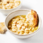 Two matching, white bowls are filled with beans, broth, and torn pieces of fresh bread.