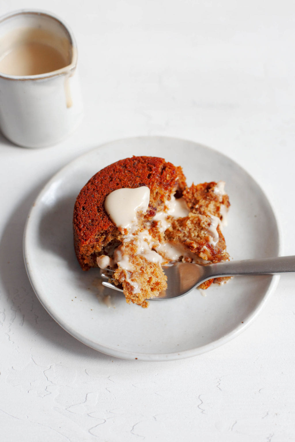 The round vegan sticky toffee pudding is covered with cashew cream and cut into small pieces with a dining fork. There is more cashew cream in a small jar at the back of the dessert.