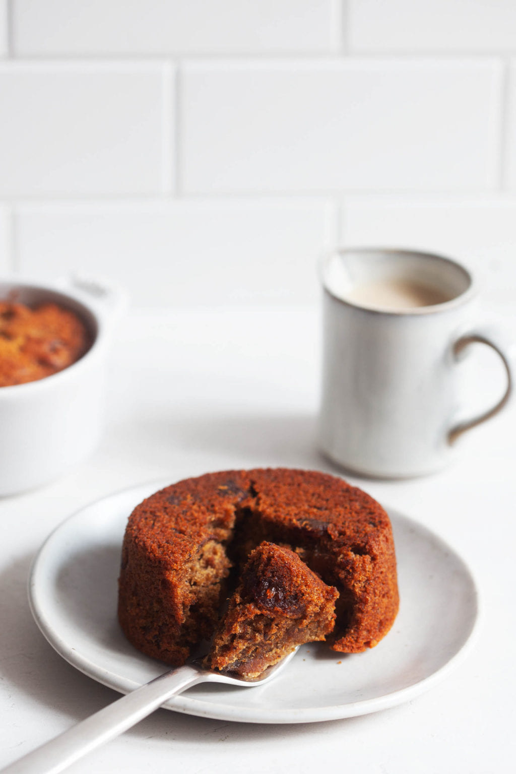 The plant-type sticky toffee pudding is placed on the dessert board, covered with dates. Cut a piece of pudding into small pieces with a fork.