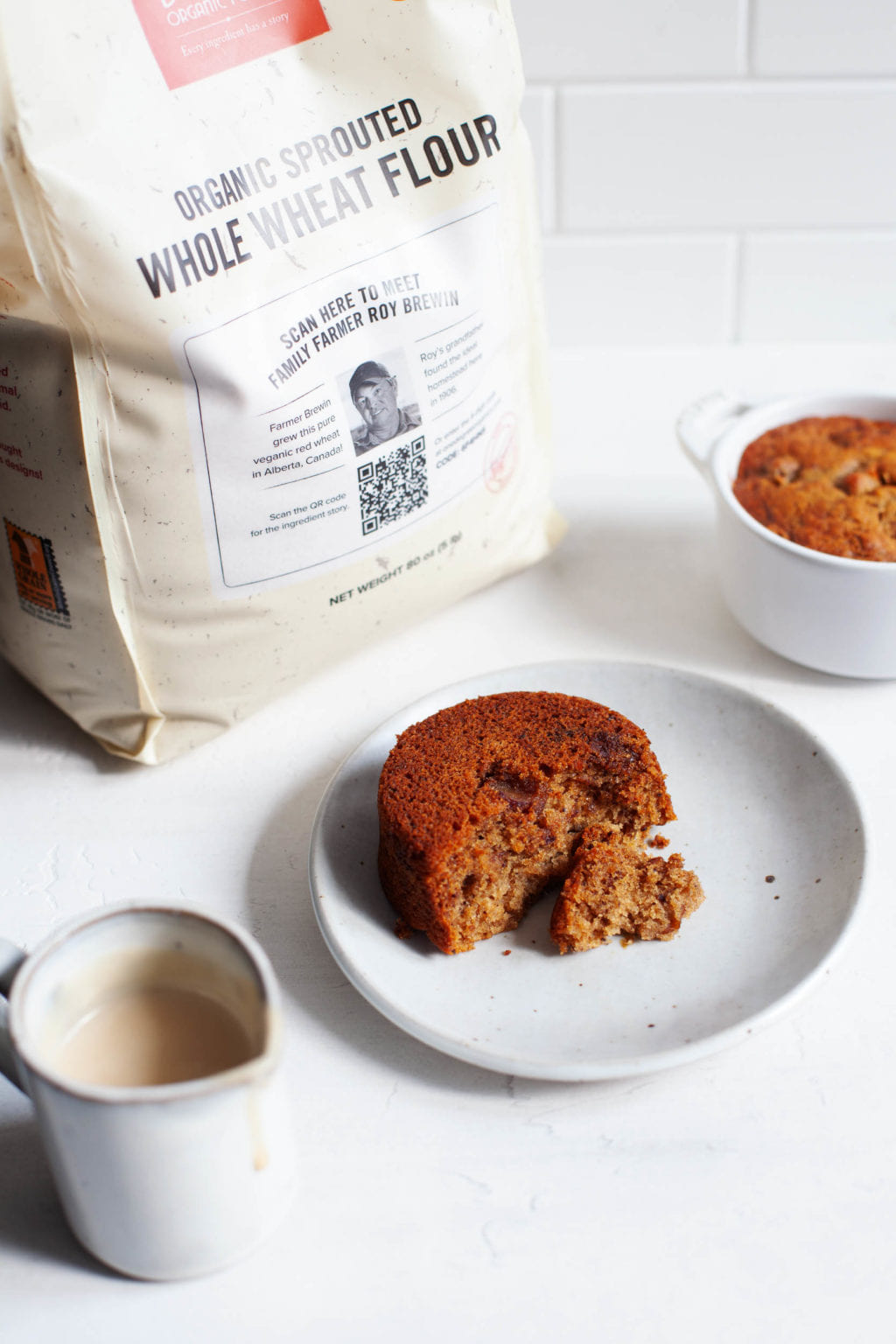A bag of whole grain flour has been used to make small round cakes, which are placed on dessert plates.
